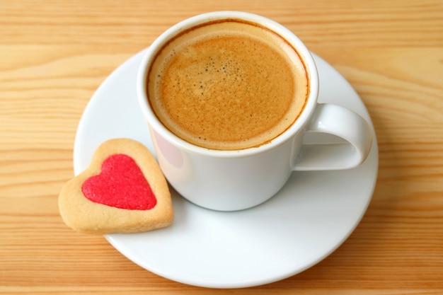 Café espresso cerrado con galletas en forma de corazón servido en una mesa de madera