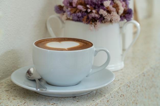 Café con espuma de leche en forma de corazón junto a la ventana con un jarrón con flores secas.