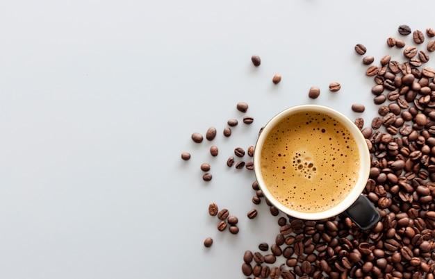 Café exprés caliente y café en grano en la mesa