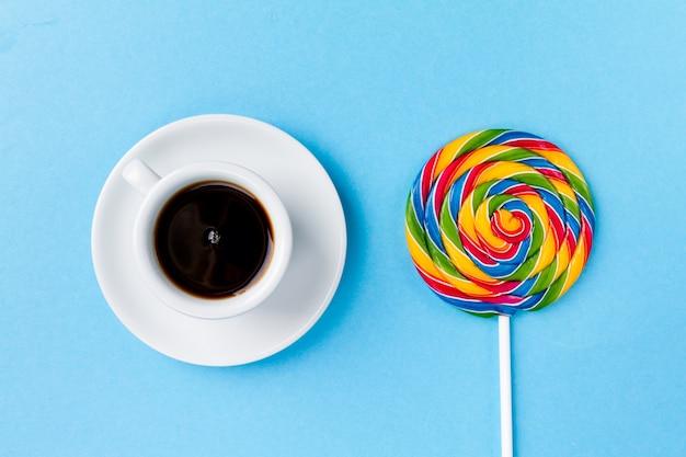 Café expreso de café de la taza con candy lollypop desayuno en fondo de mesa azul brillante