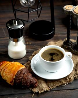 Café expreso caliente con croissant en la mesa