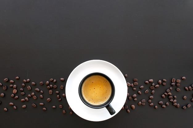 Café expreso caliente y grano de café en la mesa negra