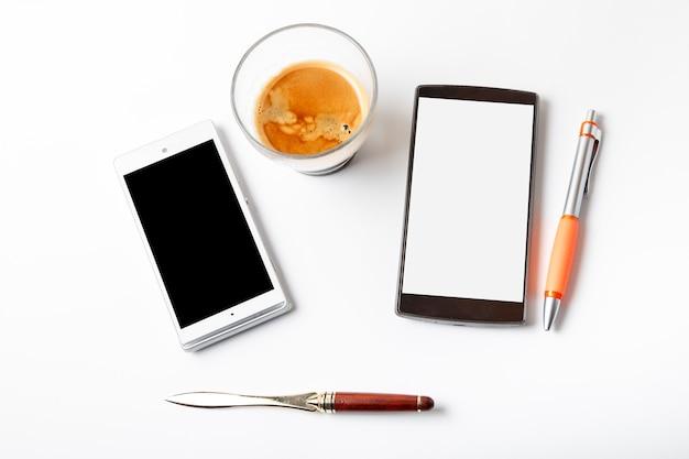 Café expreso y móvil sobre una mesa blanca.