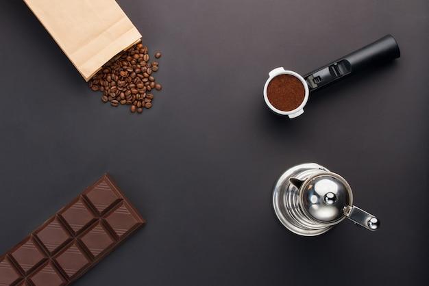 Café expreso en soporte, granos de café, barra de chocolate, cafetera
