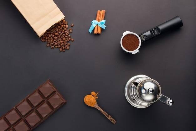Café expreso en soporte, granos de café, barra de chocolate, canela, cafetera
