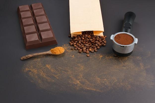 Café expreso en soporte, granos de café, barra de chocolate y cucharada de canela