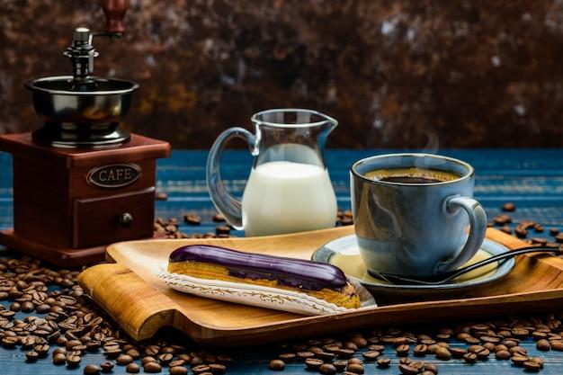 Café francés con crema y eclair y granos de café.