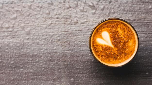 Café fresco con el arte del latte del corazón en el telón de fondo gota de agua