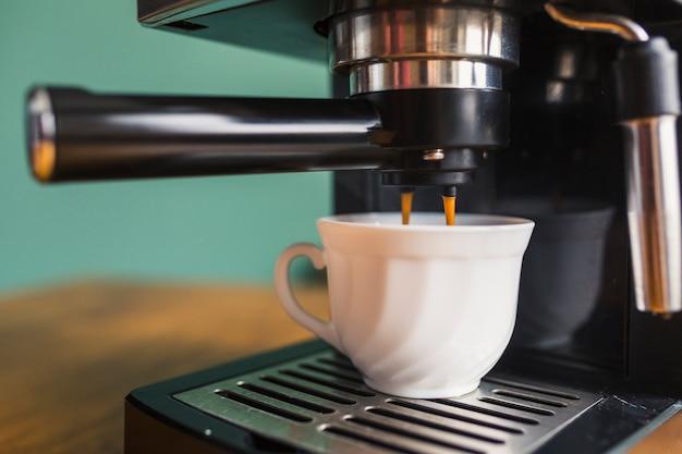 Café fresco vertiendo en taza de cerámica