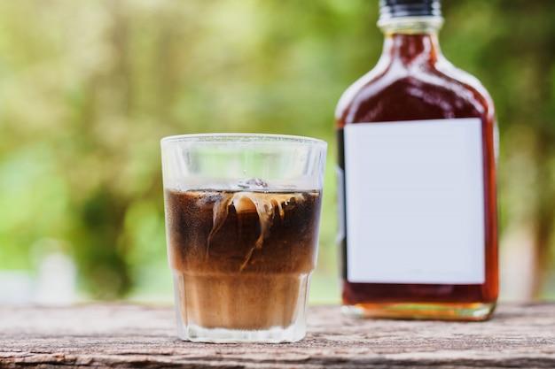 Café frío con leche en una mesa afuera con café frío en una botella de vidrio para llevar