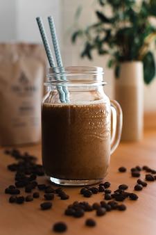 Café frío con pajitas azules rodeado de granos de café.