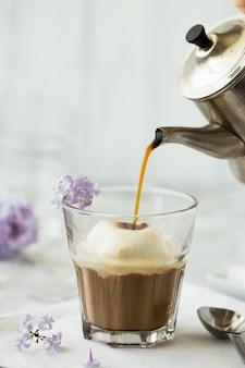 Café glaseado en vidrio. sabrosa bebida caliente llena de cafeína con espuma de leche en la parte superior.