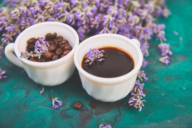 Café, grano de café en tazas y flor de lavanda sobre fondo verde