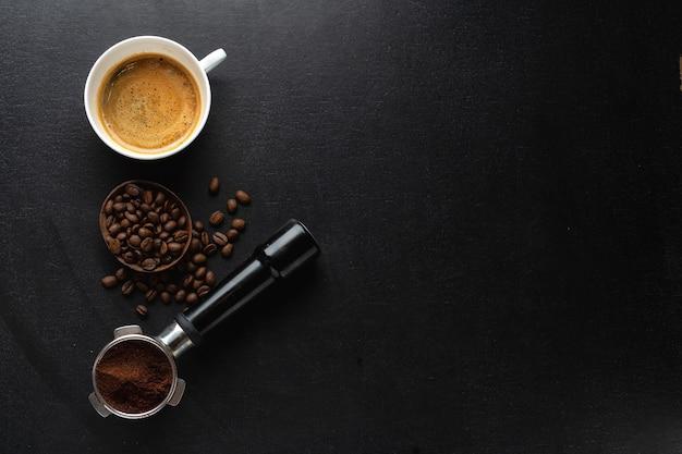 Café con granos de café, café y cuchara en la oscuridad