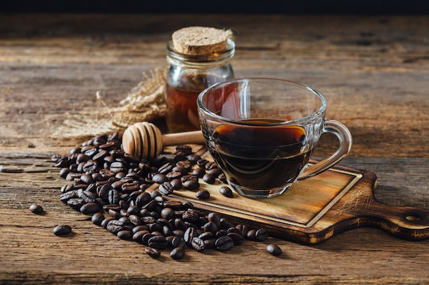 Café y granos de café con miel en mesa de madera