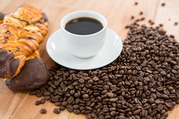 Café con granos de café tostados y croissant