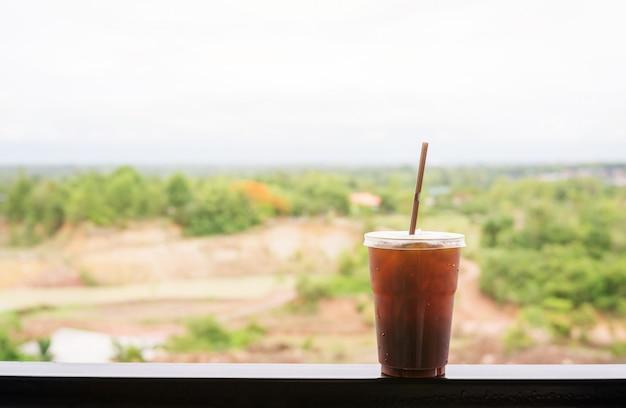 Café helado del americano en fondo de la naturaleza.