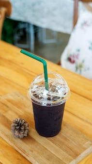 Café helado de americano en una tabla de madera en un café.