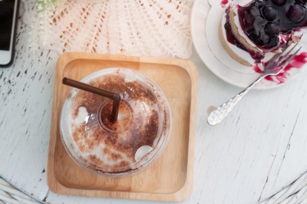 Café helado y delicioso pastel de arándanos en mesa de estilo vintage. vista superior