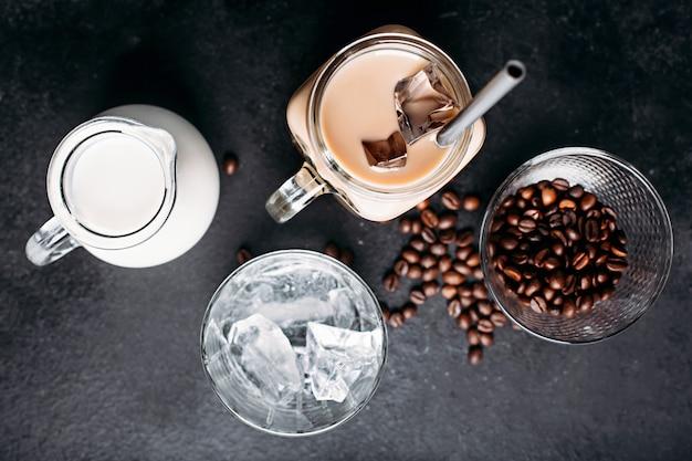 Café helado frío con ingredientes: cubitos de hielo, leche, granos de café.
