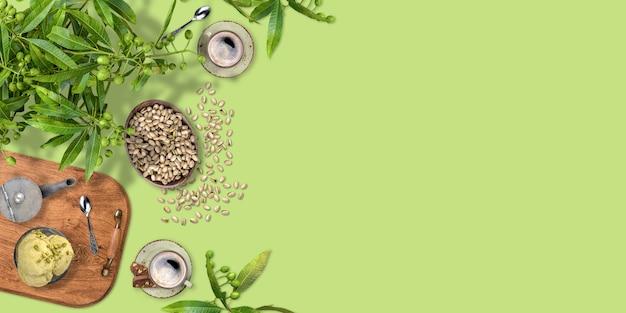 Café, helado, pistachos y rama de olivo sobre fondo verde con espacio de copia, diseño de diseño plano