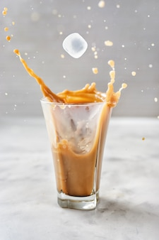 Café helado con salpicaduras sobre vidrio sobre fondo gris