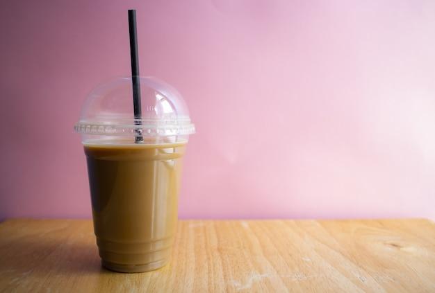 Café helado sobre una superficie de madera con una pared rosa