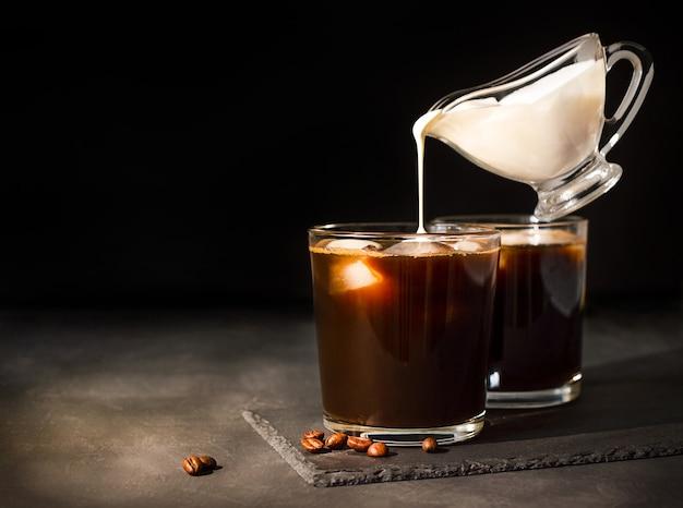 Café helado en un vaso con crema vertida. salsera con levitación de leche.