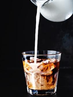 Café helado en un vaso con hielo y jarabe de azúcar