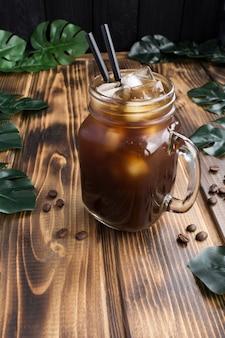 Café helado en el vaso de mesa de madera