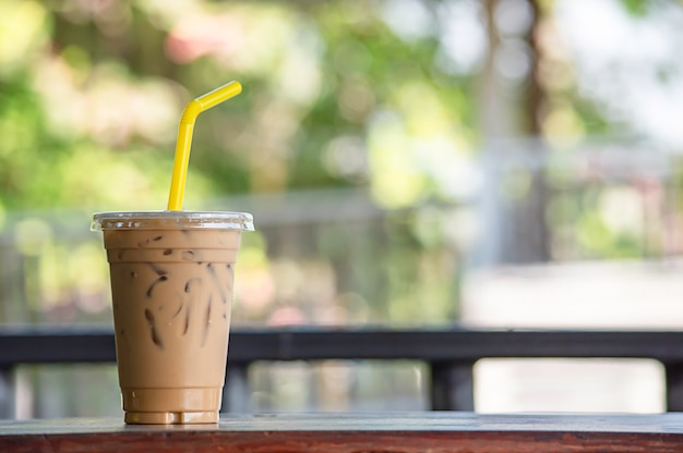 Café helado en un vaso en la mesa de madera.