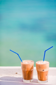 Café helado de verano frappuccino, frappe o latte en un vaso alto en el mar en el bar de la playa