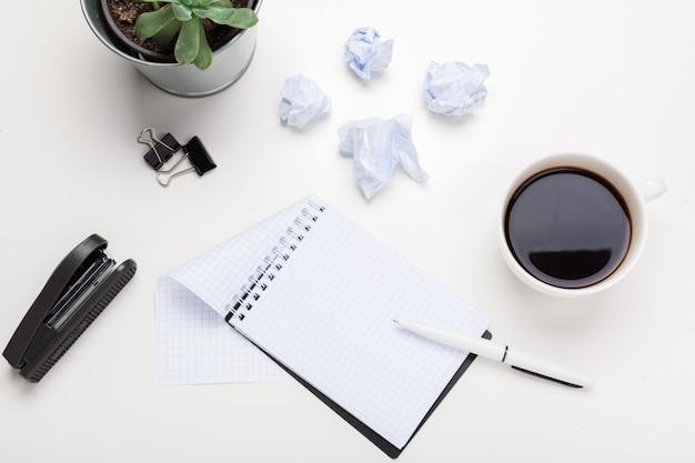 Café, hojas de papel y tacos arrugados sobre la mesa
