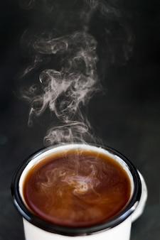 Café humeante con leche en taza