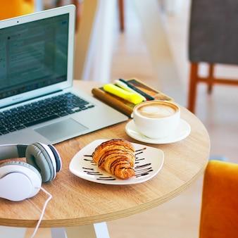 Café, laptop y croissants para mostrar un desayuno de negocios en la mesa de la oficina por la mañana.