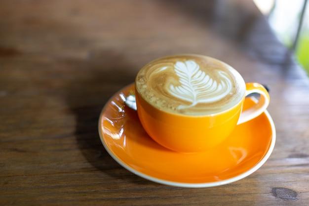 Café con leche caliente con arte tardío en aislante superior en mesa de madera