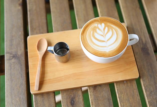 Café con leche caliente con patrón de corazones y jarabe en mesa de madera