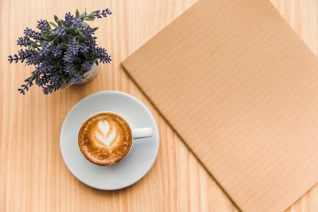 Café con leche con flor de lavanda y cuaderno sobre fondo de madera