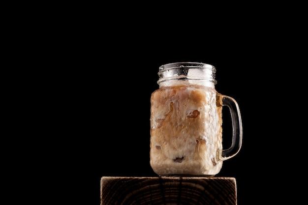 Café con leche helado en vaso sobre fondo negro. primer plano, copie el espacio.