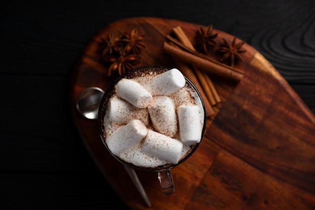 Café con leche y malvavisco con canela y anís en la vista superior de la pared de madera