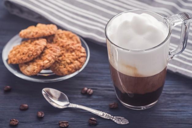 Café con leche en la mesa de madera. foto tonificada