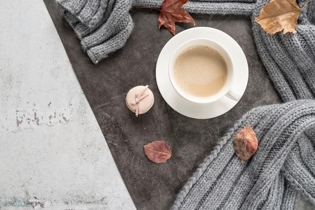 Café con leche y suéter caliente en superficie cutre.