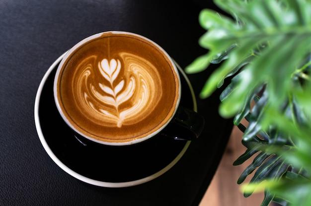Café con leche en taza negra con hojas de plantas en la mesa
