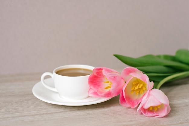 Café con leche en taza y platillo de porcelana blanca un ramo de tulipanes rosas primaverales día de la madre