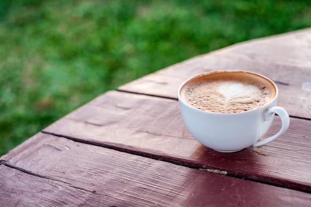 Café con leche en taza sobre mesa de madera y césped verde
