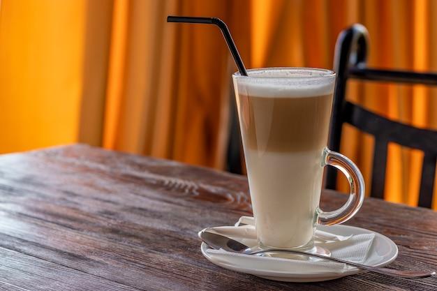 Café con leche en un vaso sobre una mesa de madera, espacio de copia