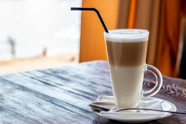 Café con leche en un vaso sobre una mesa de madera, foto horizontal, espacio de copia
