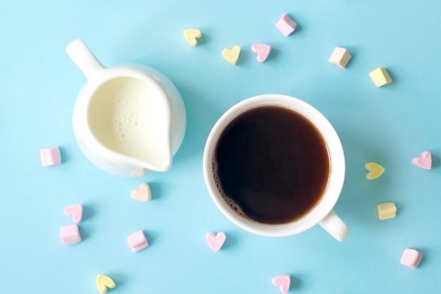 Café y lechero con leche sobre una superficie azul con muchos corazones dulces, vista superior