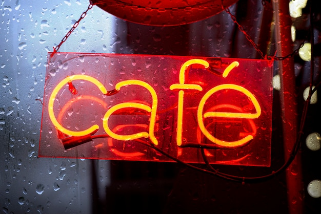 Cafe letrero rojo de neón durante la noche de fuertes lluvias, letrero electrónico para cafe