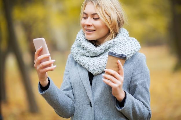 Café para llevar. mujer joven con café en el parque otoño